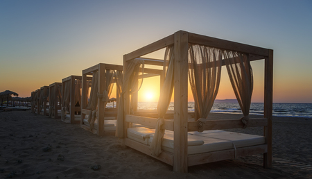 Silhouette wooden with blinds gazebo on an empty sandy beach on a sunset background. Stok Fotoğraf