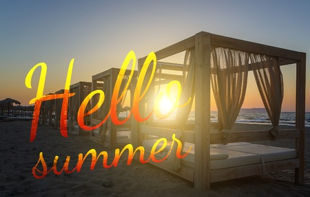 Text Hello Summer on silhouette wooden with blinds gazebo on an empty sandy beach on sunset background.
