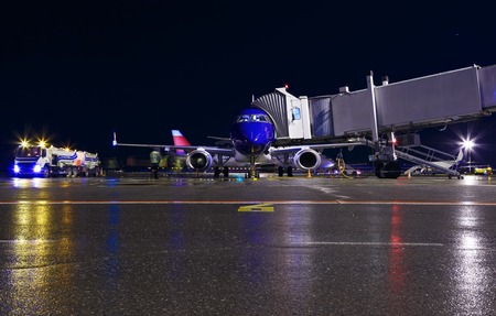 blue modern aircraft maintenance night airport , fuel truck, jet bridge and the staff people. Completely white passenger plane before flight. Aircraft is parked at the night airport. Front view.
