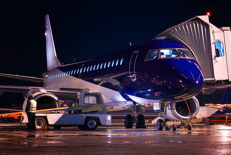 Passenger blue-body plane at night airport. Preflight aircraft service before departure. Loading meal and luggage on board. Boarding bridge docked with Airplane.