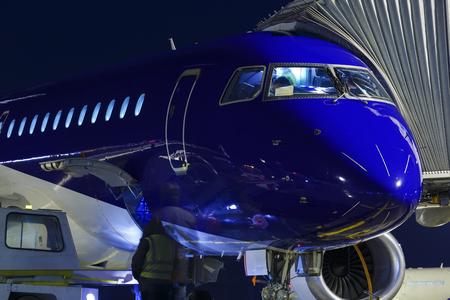Avión estacionado en el aeropuerto y preparación para el próximo vuelo. Carga de carga en el avión en la terminal del aeropuerto por la noche. Servicio de avión de carga para trabajadores.