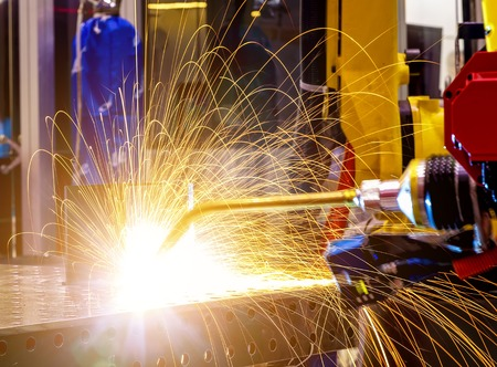 industrial yellow robot welder close up conduct welding of metal parts, metal droplets are beautifully sprinkled in all directions