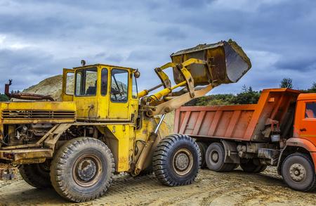Loader graafmachine laadt de grond in vrachtwagen bij de wegenbouw
