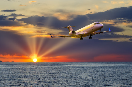 private business jet plane flying over the sea at sunset, the suns rays cut through the clouds