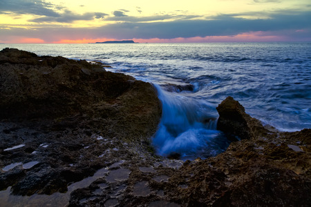 sunset over the sea, pink clouds, rocks in the foreground, which is flooded with a wave Stock Photo