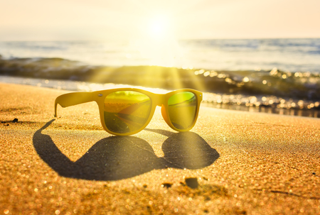 suns rays cut through the stylish yellow sunglasses on the edge of the shore near the waves on sand.