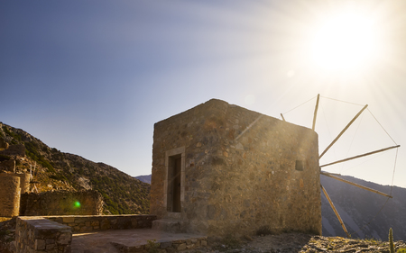 An old stone mill on top of a mountain, against the backdrop of a mountain range and valley. suns rays cut through the sky and the mill