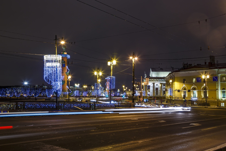 One of bridges of Vasilievsky island with tracers from car headlights, night Christmas illumination, road in the foreground.