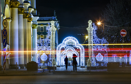 tourists are photographed against the illumination of the winter Palace of the Hermitage St. Petersburg, tracers from cars