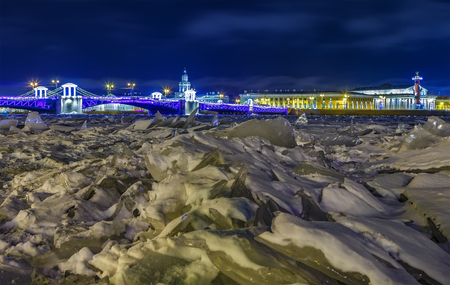 Winter view of decorated Palace bridge in St. Petersburg. Illuminated Palace bridge over frozen Neva river in winter night is tourist attraction.
