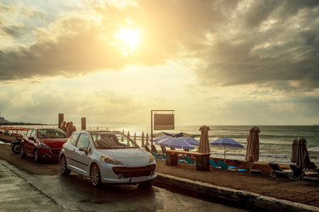 Famous tourist destination in Crete, Gouves, promenade near the beach and the sea, sunset, clouds sun Standard-Bild