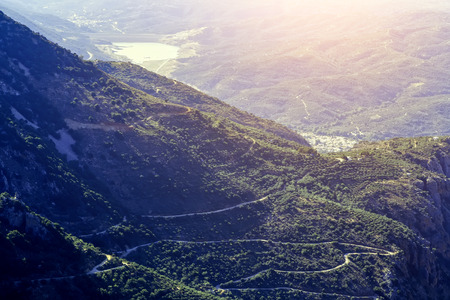 slope of the mountain near the Lassithi plateau with views of the lake and the village , the setting sun, the evening. Crete Greece. Sun valley of Greece. Beautiful Lassithi Plateau on island of Crete, Greece. Stock Photo