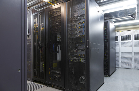 Network server room with parallel rows of mainframe. Corridor in big working data center full of rack servers and supercomputers. Networking and technology futuristic concept