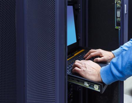 Sluit de handen van de systeembeheerder die computerapparatuur in de serverruimte controleert. Technicus aan het werk in een modern datacenter