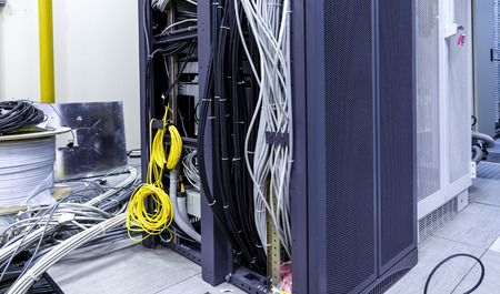 Racks with servers, computer equipment and connected twisting and coiling internet wires, patch cord optic cables located in data center.