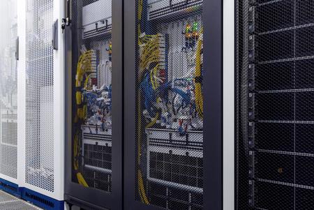 Zamknij szafę serwerową ze wskaźnikiem LED, przewodami internetowymi, kablami światłowodowymi wewnątrz pod drzwiami z siatki. Serwer komputerowy w szafie, sieci i sprzęcie. Wnętrze centrum danych. Zaplecze technologiczne