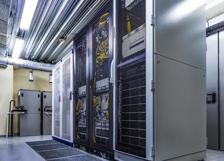 Pomieszczenie z szafą serwerową sprzętu, przechowywanie w chmurze w dużym centrum danych. Sprzęt techniczny i superkomputery z podłączonymi przewodami i kablami w szafach pod zamkniętymi drzwiami kratowymi