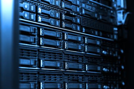 Chiudere il rack e l'archiviazione dell'attrezzatura del server blade in un grande centro dati. Sfondo tecnologico con cornice laterale sfocata tonalità blu freddo Archivio Fotografico