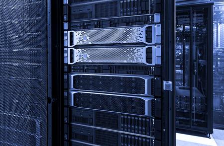 Racks de servidores con discos de mainframe, almacenamiento en la nube, tonos neón azul