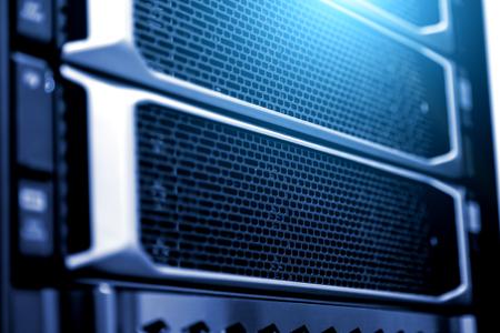 Supercomputer-Server-Racks im Rechenzentrumsdetail schließen vermaschte Festplattenabdeckung verschwommene Rahmentiefe des Feldes mit fluoreszierendem blauem Licht ab. Konzept der Array-Festplatte Big Data Storage Cloud Computing-Technologie