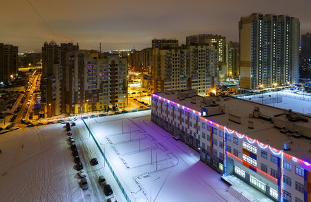 Cityscape of dormitory area of Saint Petersburg, Russia. Residential apartment and public buildings decorated with Christmas lights. Streets and car parking under snow. Winter night