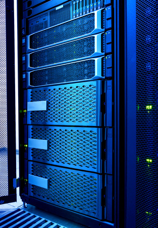 Powerful computer server in rack and raid storage in datacenter. Technical site equipment of modern internet provider. Data processing concept. Technological background with cold blue toning 免版税图像 - 124447010