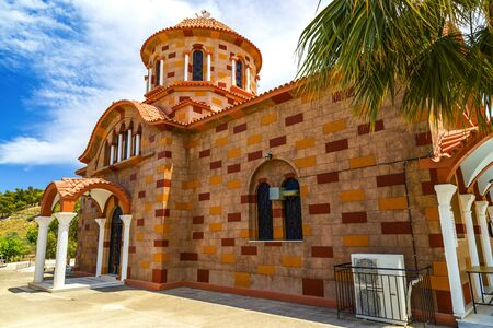 A view of a church red brick against the sky with clouds on Greek island, Greece