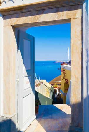 door open with a sea view, from a courtyard in Santorini, Greece