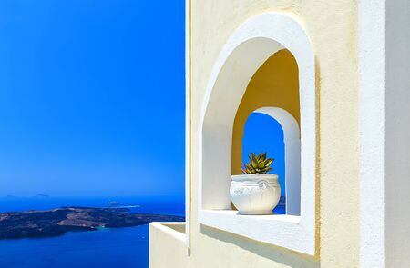 Greece Santorini island in Cyclades, traditional detail sights of colorful flowers with pots and caldera sea in the background Фото со стока