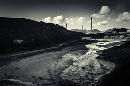 Chimneys of copper smelting plant. dirty river water after factory waste with piles of black waste on the background of pipes and factory workshops. Environmental disaster, black and white photo