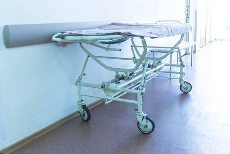 trolley voor patiënten in de ziekenhuisgang, fel licht uit het raam. Blauwe tinten