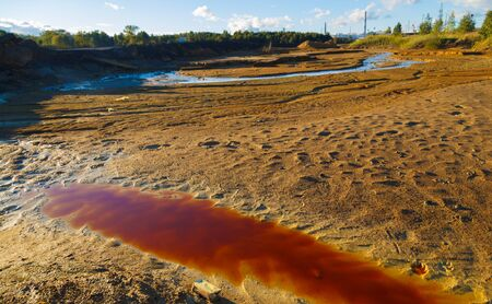 River with polluted red toxic water and soil and with garbage on the shore. environmental pollution by the factory