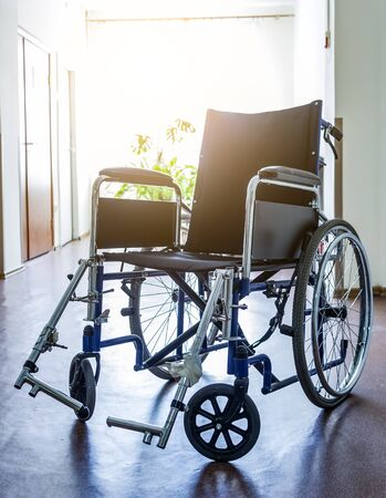 wheelchair empty in the corridor of the hospital on the background of the window from which the sun shines