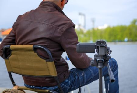 Close up of video camera filming young male blogger at the city pond