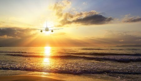 Airplane flying over blur tropical beach bokeh sun light wave and sunset sky abstract background. Copy space of business summer vacation and travel adventure concept. Vintage tone filter effect color. Stock fotó