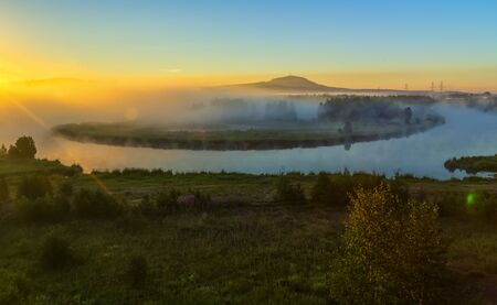 Morning foggy landscape with curved river and green hills. Summer misty Elbe river and low mountains