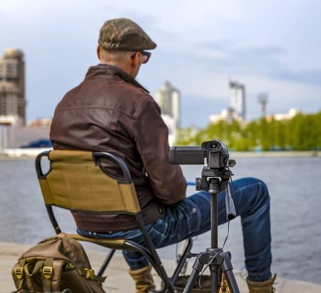 Close up of video camera filming young male blogger at city pond. depth of field blur.