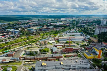 industrial zone aerial view, beautiful landscape and clouds on horizon. Summer, view from drone