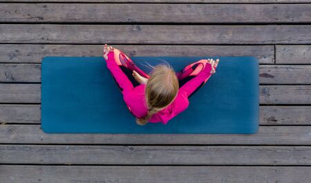 Top view of beautiful young fitness woman working out on wooden floor terrace, doing yoga exercise, full length. Banco de Imagens