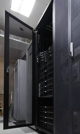 Server rack in big data center inside close up. Supercomputer with hardware, storage blades, cables and wires. Datacentre interface with door opened