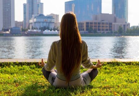 young athletic girl in yoga pose on the waterfront of the city pond, Sunny summer weather Banco de Imagens