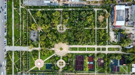 Aerial shot of beautiful metropolitan Park with tree paths, sports grounds