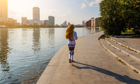 Running woman. Runner is jogging on sunrise. Female fitness model training outside in the city on a quay. Sport lifestyle. Banco de Imagens