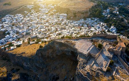 Aerial birds eye view drone photo of village Lindos, Rhodes island, Dodecanese, Greece. Sunset panorama with castle, Mediterranean sea coast. Famous tourist destination in South Europe