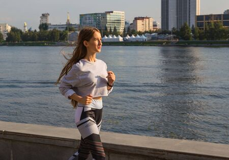 Fit young woman running on the boardwalk along river. Caucasian female athlete training outdoors by waterfront.