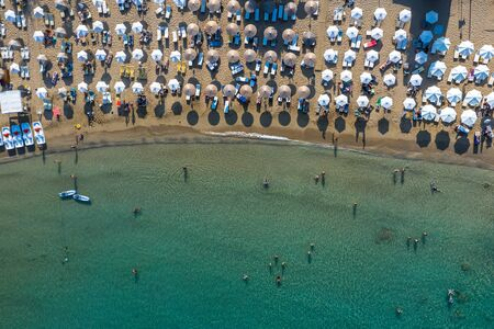 Aerial top view photo of sun beds and umbrellas in popular tropical paradise deep turquoise Mediterranean sandy crowded beach.