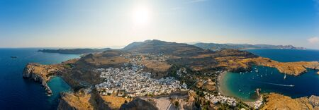 Breathtaking panoramic aerial view of Lindos town from the Acropolis of Lindos in Rhodes, Greece. Amazing colorful sunset scenery in Rhodes. Idyllic background above the Aegean sea. Dodecanese, Greece Banque d'images - 132764049