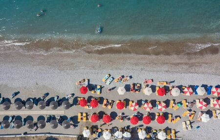 Tropical beach with colorful umbrellas - Top down aerial view. Rhodes Greece