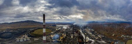 panorama of copper production plant in Karabash, Chelyabinsk region, environmental disaster, pollution, smoke from pipes on the background of mountains.