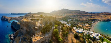 Breathtaking panoramic aerial view of Lindos town from the Acropolis of Lindos in Rhodes, Greece. Amazing colorful sunset scenery in Rhodes. Idyllic background above Aegean sea. Dodecanese, Greece.